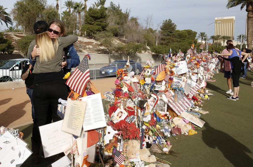 Las sobrevivientes de tiro de Las Vegas Kristy-Marie Hoff, izquierda, y Shawna Bartlett se abrazan mientras visitan un monumento conmemorativo de víctimas de tiroteo de la Ruta 91 en el letrero d ...