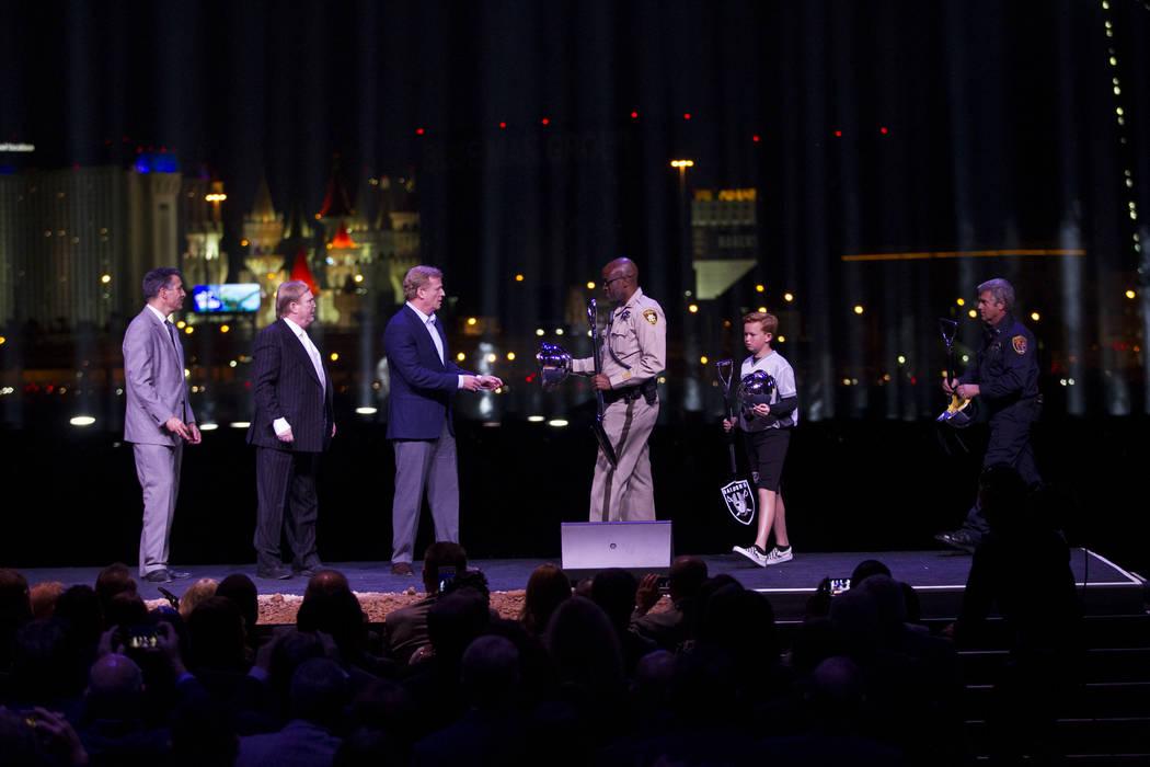 El gobernador Brian Sandoval, desde la izquierda, el dueño de los Raiders, Mark Davis, y el comisionado de la NFL, Roger Goodell, reciben cascos ceremoniales y palas de personas que incluyen pers ...
