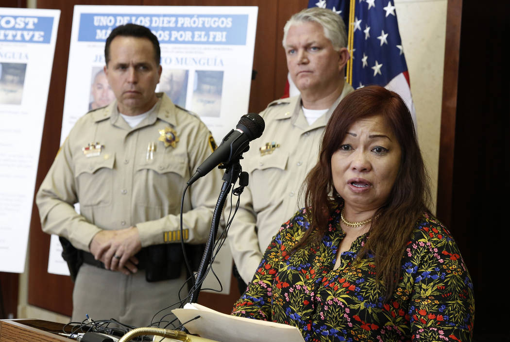 Noema González, madre de la víctima de asesinato Sherryl Sacueza, habla mientras el ayudante del alguail Tom Roberts, izquierda, observa durante una conferencia de prensa donde el FBI anunció l ...