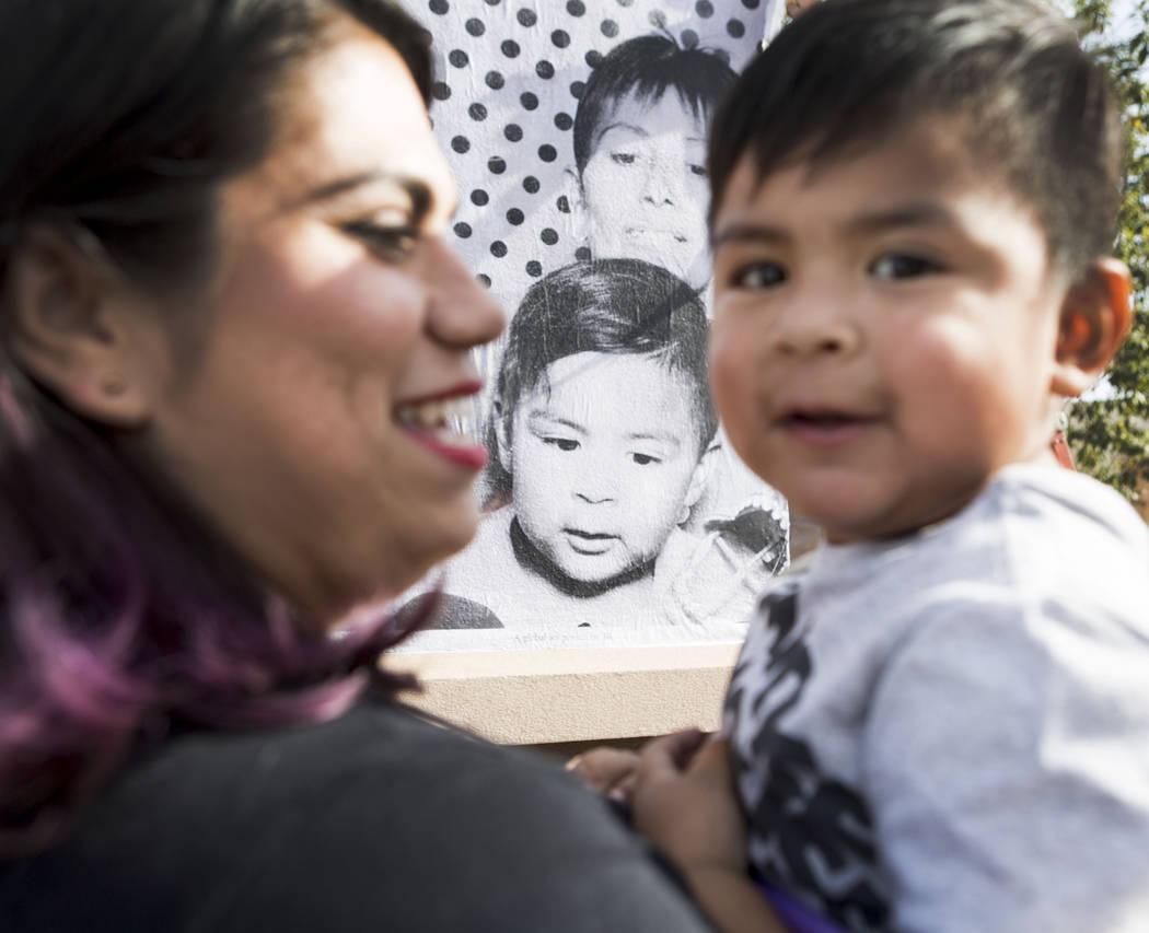 Astrid Silva, a la izquierda, sostiene a su sobrino Noah, de 2 años, frente a un retrato impreso a gran escala del camión Inside Out Project que se detuvo en el East Las Vegas Community Center e ...