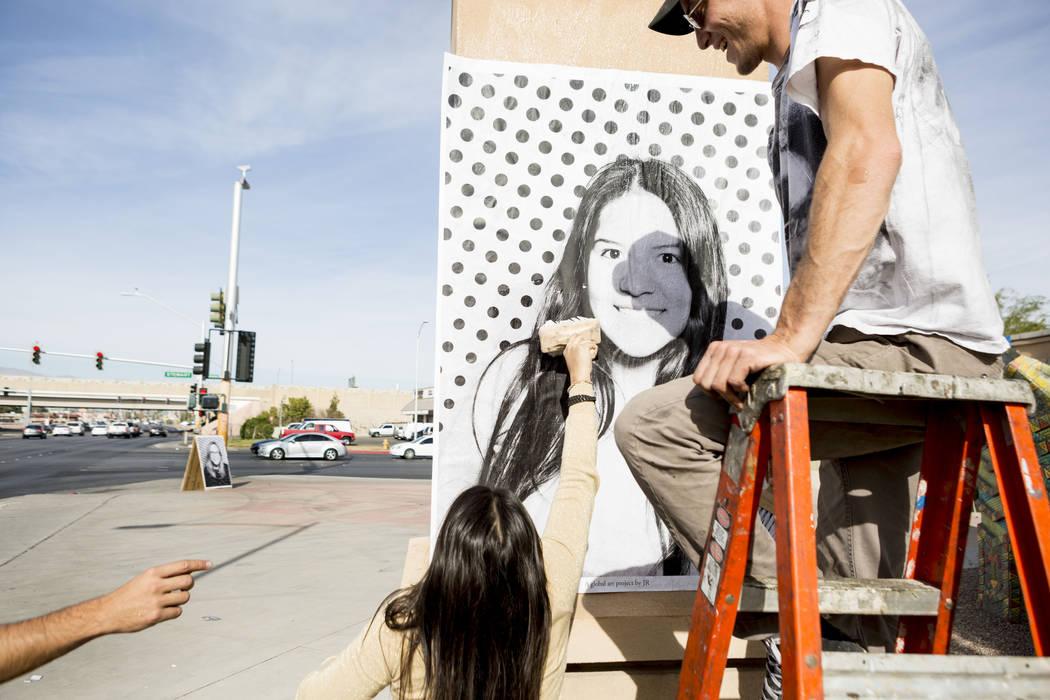 Angela Rebaza, izquierda, originaria de Perú que ahora reside en Las Vegas, ayuda a Alexander Pierre con el proyecto Inside Out a pegar su impresión a gran escala para celebrar a los beneficiari ...