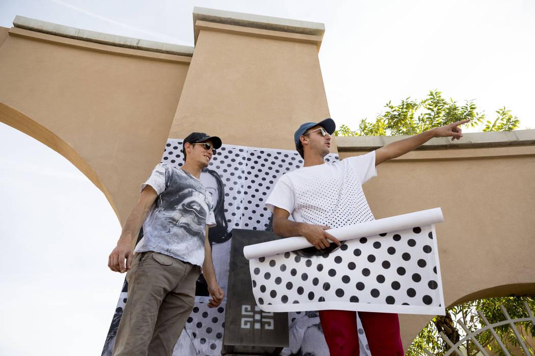 Alexander Pierre, izquierda, y Marz Holden-Montini, con el Proyecto Inside Out para Dreamers pegan grandes fotografías de los beneficiarios de DACA en el Centro Comunitario East Las Vegas en Las  ...