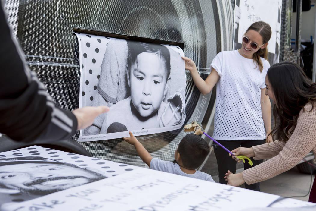 Noah, de 2 años, al centro, busca una impresión a gran escala de él mismo en el camión Inside Out Project que se detuvo en el East Las Vegas Community Center en Las Vegas para celebrar a los b ...