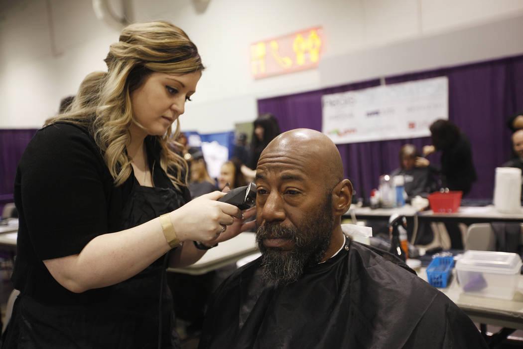 Sheila Rees recorta la barba de Brigham Roberts en Project Homeless Connect, una feria de servicios y recursos para personas sin hogar o en riesgo en el Cashman Center de Las Vegas, el martes 14 d ...