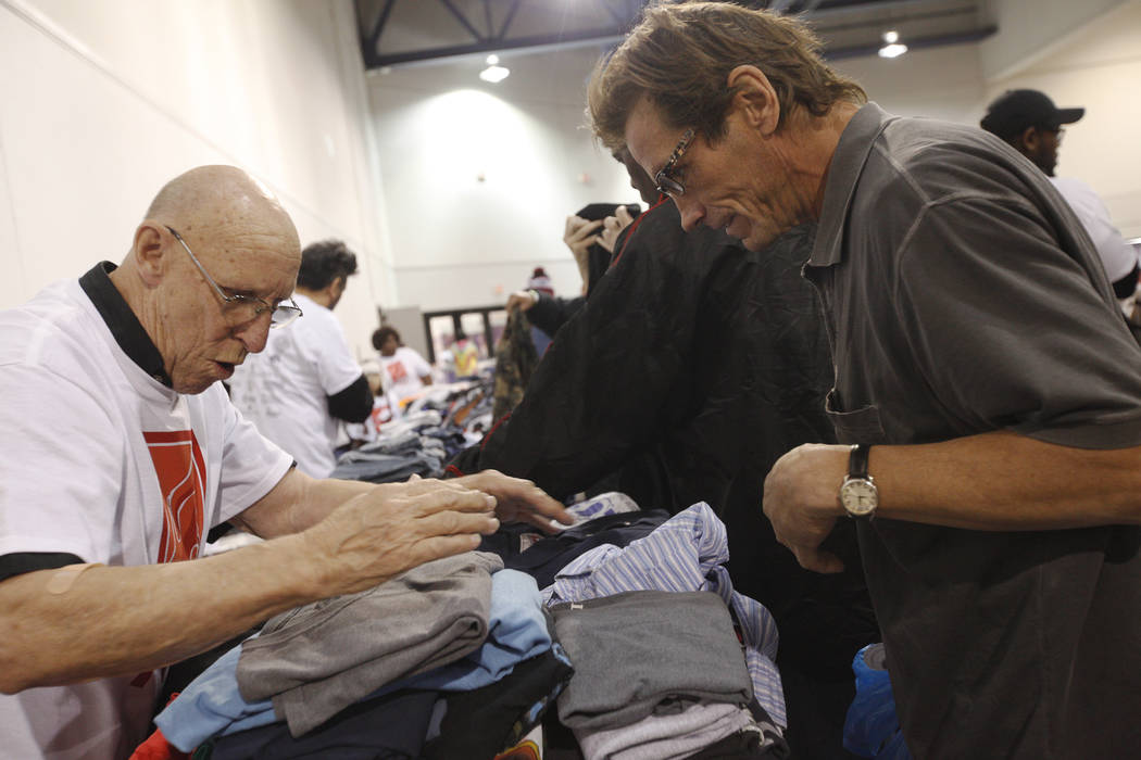 El voluntario Bill Corzatt, izquierda, ayuda a Lawrence Green a buscar pantalones en Project Homeless Connect, una feria de servicios y recursos para personas sin hogar o en riesgo en el Cashman C ...