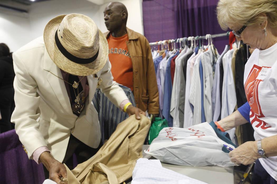 Kevin Washington extiende su nueva camisa y artículos con la ayuda de la voluntaria Shirley Hartung en Project Homeless Connect, una feria de servicios y recursos para personas sin hogar o en rie ...