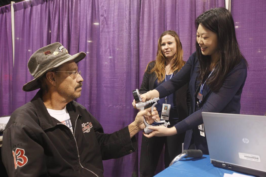 El veterano Richard Palmer tiene su fuerza en la mano probada por Sora Julie Lee en Project Homeless Connect, una feria de servicios y recursos para personas sin hogar o en riesgo en el Cashman Ce ...