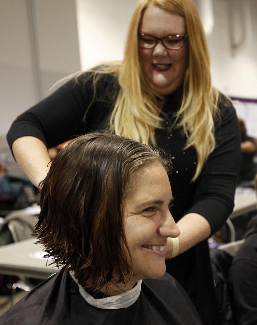 Julia Keogh le corta el pelo a Joy Simon en Project Homeless Connect, una feria de servicios y recursos para personas sin hogar o en riesgo en el Cashman Center de Las Vegas, el martes 14 de novie ...