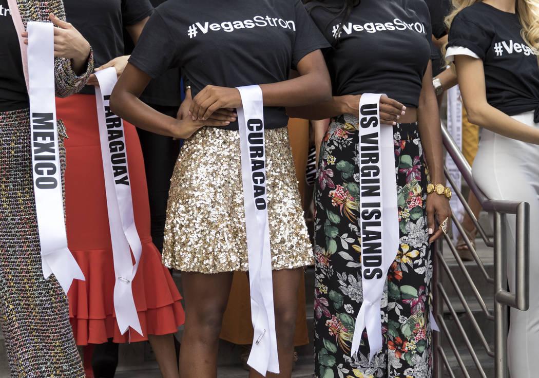 Los concursantes de Miss Universo retiran sus bandas para honrar a las víctimas del tiroteo de la Ruta 91 durante un evento de bienvenida para las concursantes en el Planet Hollywood Resort en La ...