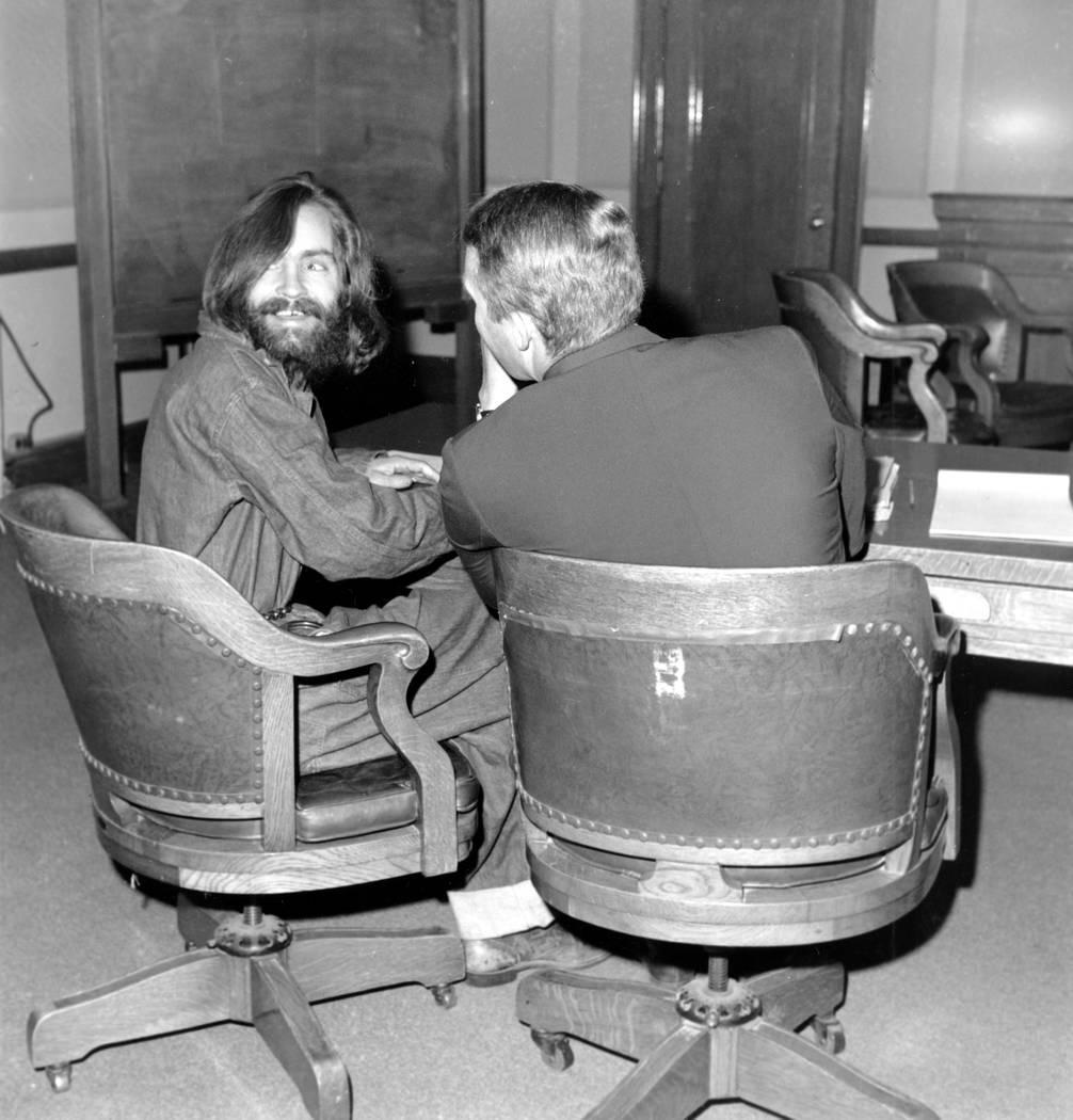 El líder de culto Charles Manson mira hacia atrás y sonríe mientras su abogado, el defensor público Fred Schaefer, habla con él en Independence, California, el 4 de diciembre de 1969. Manson  ...