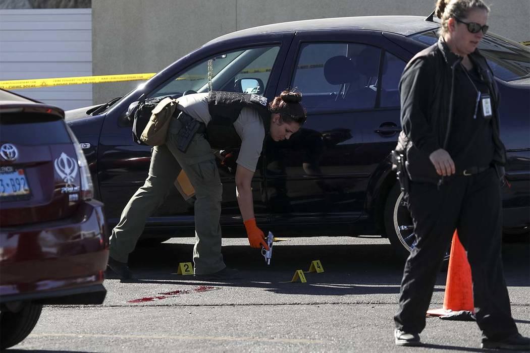 Los investigadores de la escena del crimen recogen un arma como evidencia en la escena de un tiroteo ocurrido en un callejón detrás de una tienda 7-Eleven cerca de la intersección de East Sunse ...