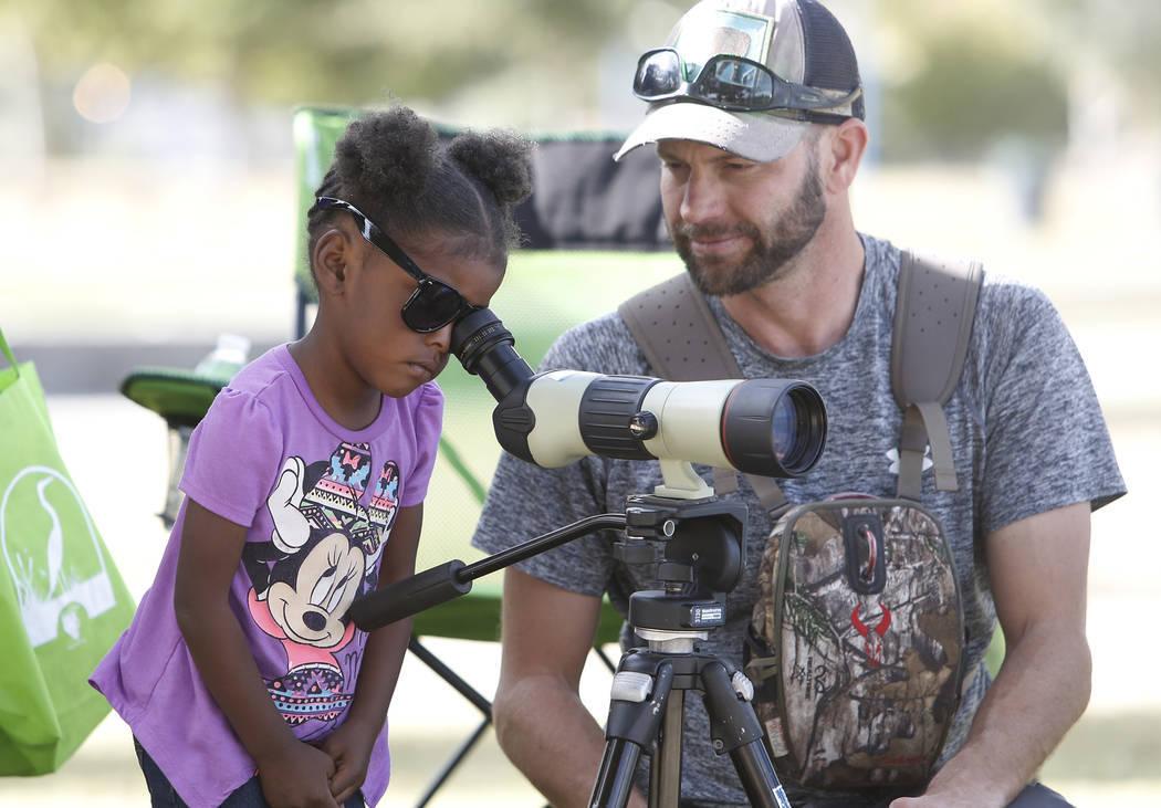 Nyriah, de 3 años, analiza el alcance de detección como lo ve Nathan Lemon, un biólogo de la Oficina de Recuperación, durante el Día Internacional de Aves Migratorias el martes 21 de noviembr ...