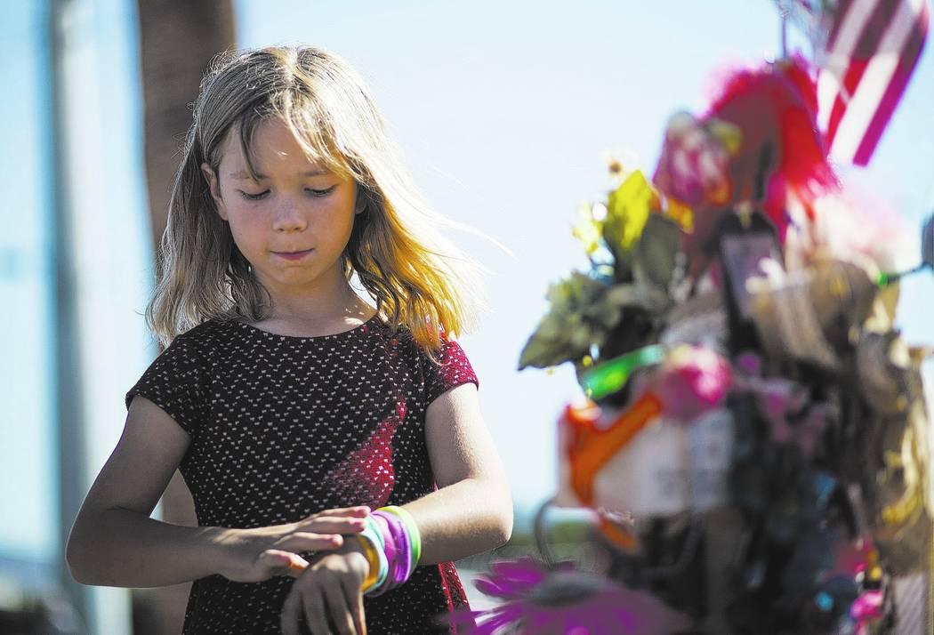 Brooke Patterson, de Lomita, Calif., De siete años, visita un monumento improvisado para su madre, Lisa Patterson, quien fue una de las 58 personas que murieron en el tiroteo del 1° de octubre e ...