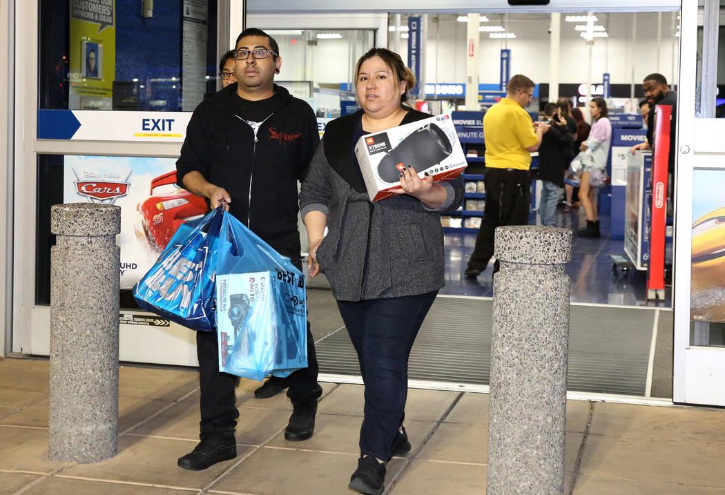 Jorge Santiago y su esposa, Lesly, salen con sus compras a la 1:04 a.m. después de las compras del Black Friday en Best Buy en Henderson el 24 de noviembre de 2017 en Las Vegas. (Bizuayehu Tesfay ...