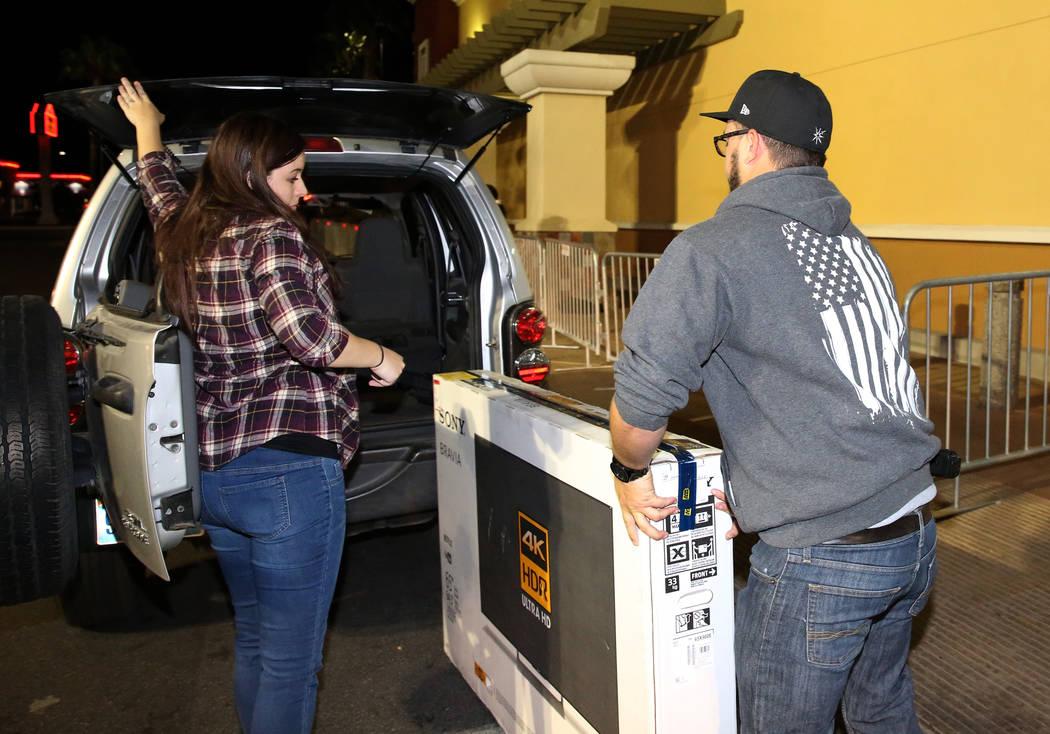 Brandon Pritchard y su esposa, Britney, cargan su TV de pantalla plana en la cajuela de una SUV a las 12:56 a.m. después de las compras de Black Friday en Best Buy en Henderson el 24 de noviembre ...
