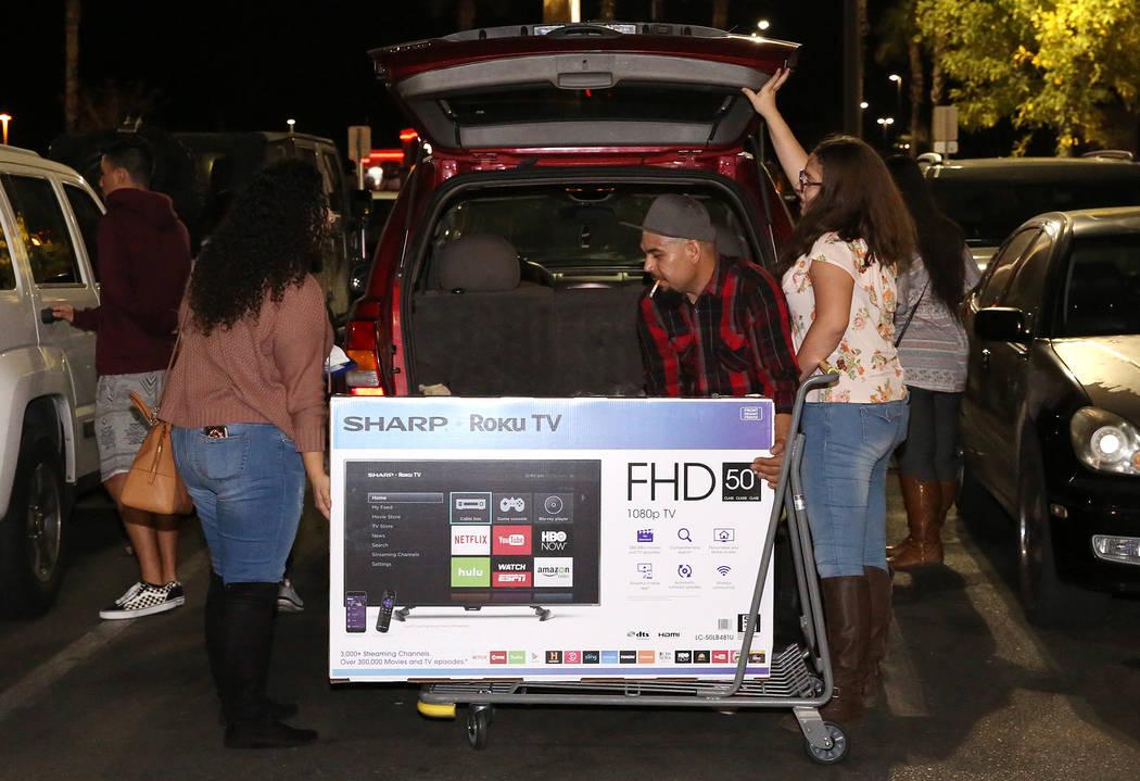Daniel López, al centro, carga su televisor de pantalla plana en el maletero de una SUV a las 12:44 a.m. después de las compras de Black Friday en Best Buy en Henderson el 24 de noviembre de 201 ...