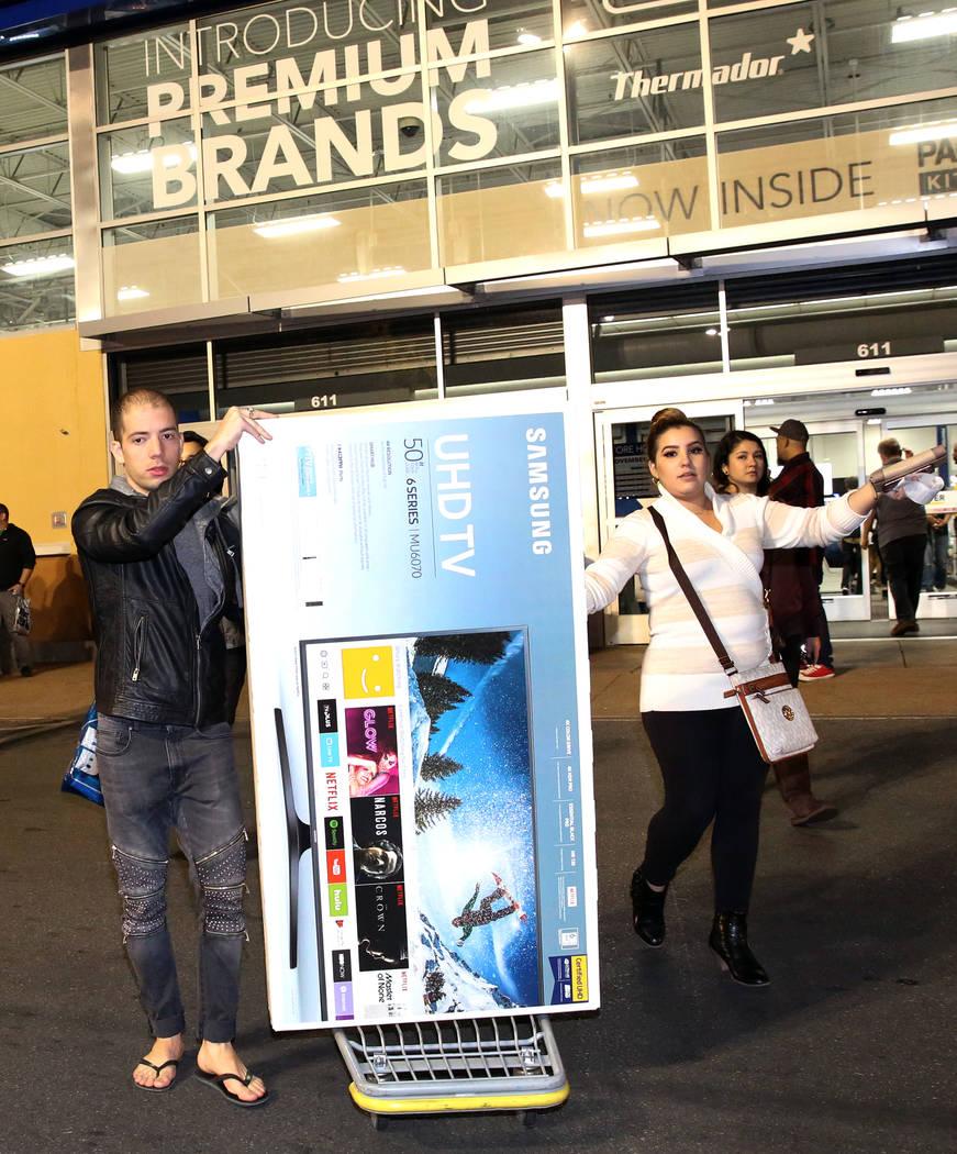 Louis Tamarit, izquierda, y Luisa Puentes salen con su compra de TV de pantalla plana a las 12:42 a.m. después de las compras del Black Friday en Best Buy en Henderson el 24 de noviembre de 2017, ...