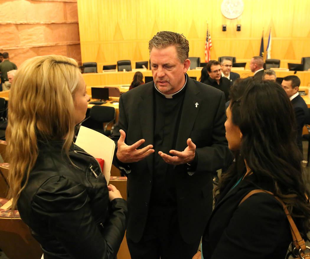 El Diácono Thomas Roberts, habla con los sobrevivientes del tiroteo en Las Vegas del 1° de octubre, Laura Puglia, a la izquierda, y Lillian Aguirre después de la reunión del ayuntamiento del C ...