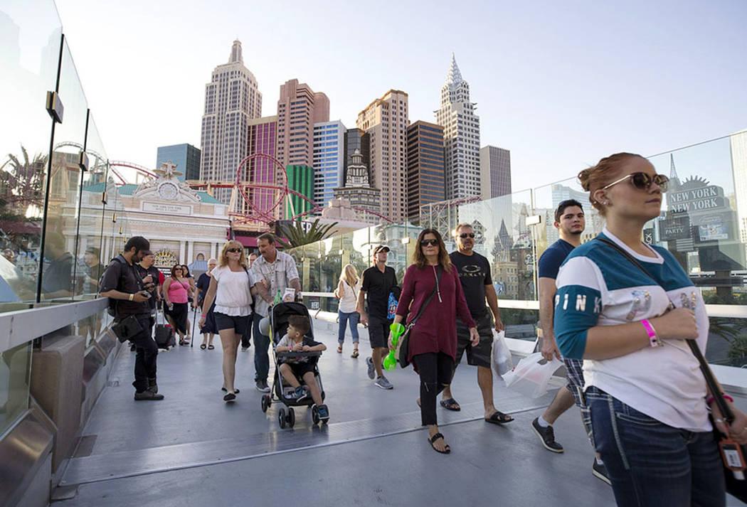 La gente camina sobre un puente peatonal que une a el New York-New York y MGM Grand cerca de la intersección de Las Vegas Boulevard y Tropicana Avenue en Las Vegas, jueves, 12 de octubre de 2017. ...