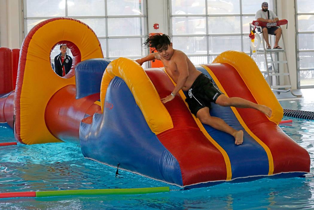 El salvavidas Reimart Yray, de 19 años, de Las Vegas, demuestra jugar en un tobogán acuático durante la gran inauguración de la piscina cubierta Aquatic Springs de 24,940 pies cuadrados en Las ...