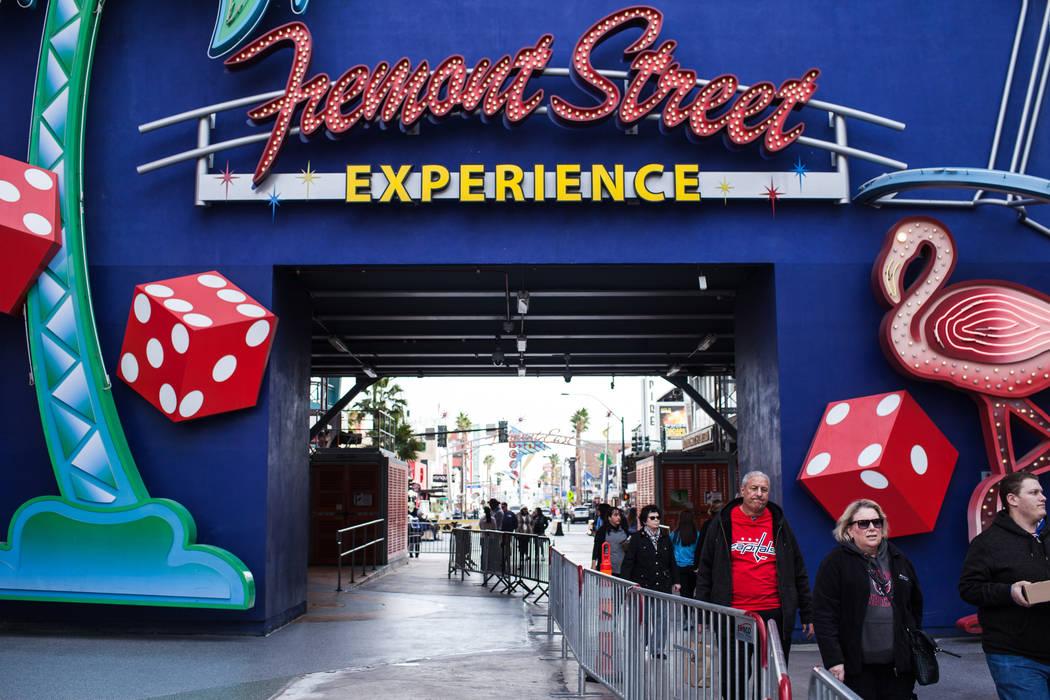 La gente camina a lo largo de Fremont Street Experience mientras se instalan barricadas en preparación para las celebraciones de la víspera de Año Nuevo en Las Vegas, el sábado 23 de diciembre ...