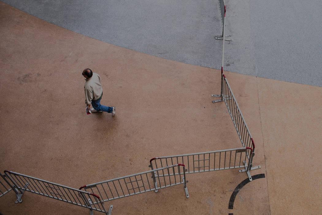 Una persona camina a lo largo de Fremont Street Experience mientras se instalan barricadas en preparación para las celebraciones de la víspera de Año Nuevo en Las Vegas, el sábado 23 de diciem ...