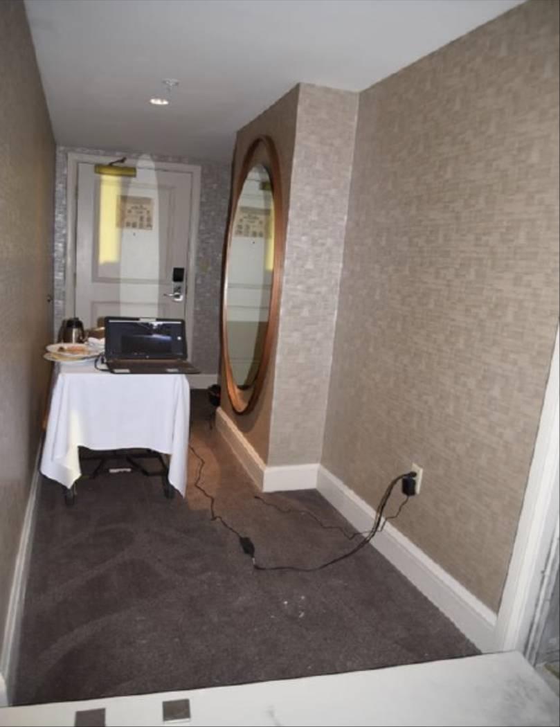 El pasillo de la habitación 32-134 con un carrito de servicio de alimentos y una computadora portátil conectados a las cámaras en el pasillo. LVMPD.