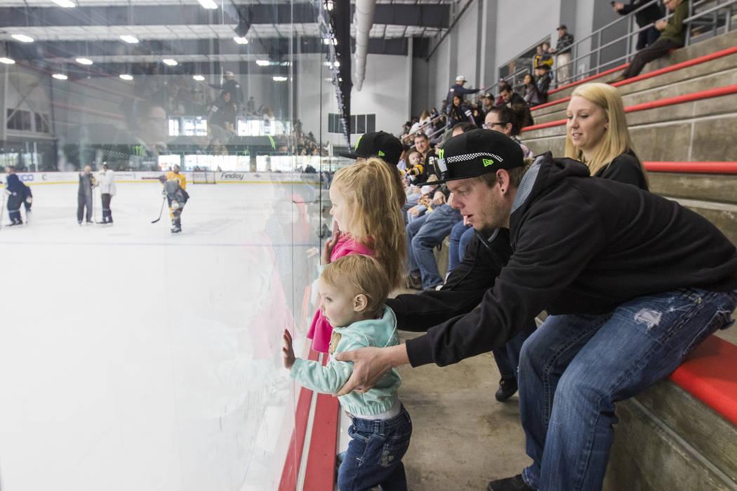 Andrew Alderman sostiene a su hija Rilyn Adlerman, de 19 meses, mientras observan a los Golden Knights de Vegas practicar junto a su esposa Holly Alderman e hijas Adeline Alderman, de 3 años, y M ...