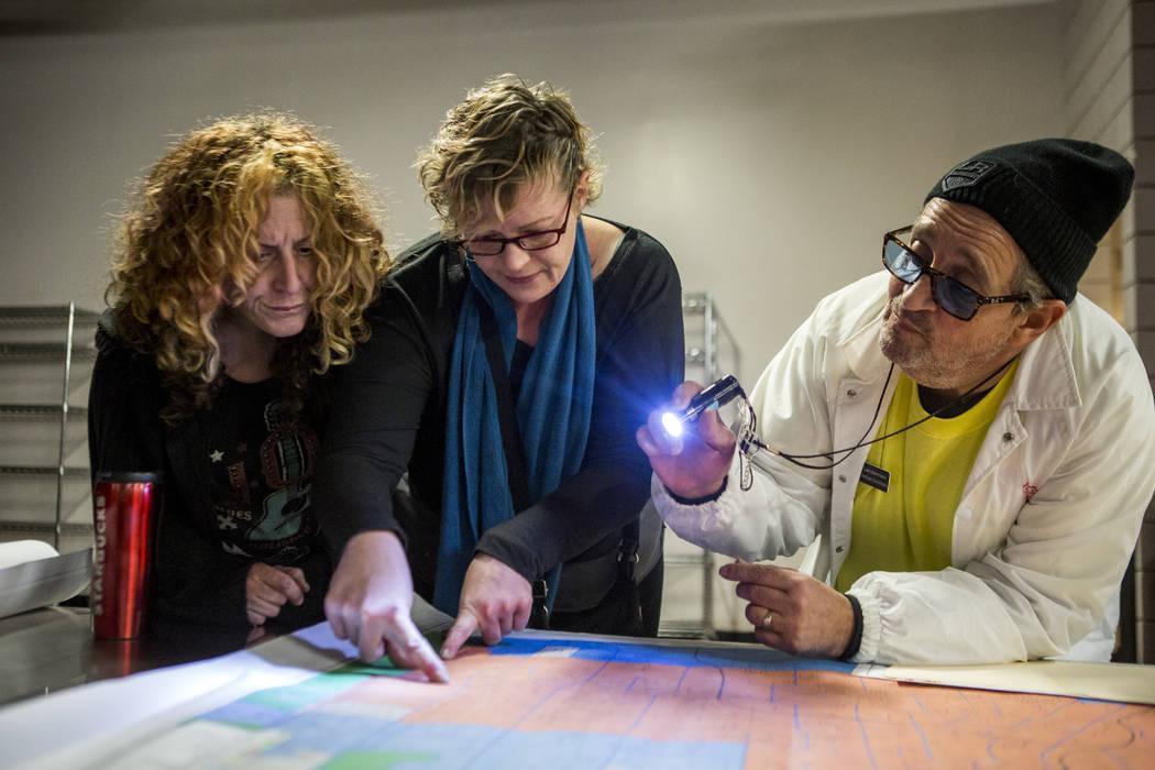 Anne Donahue, izquierda, y Brandy Glasgow, voluntarios, revisan un mapa con Nick Lenderman, un veterano coordinador de servicios para The Salvation Army, en Catholic Charities of Southern Nevada e ...