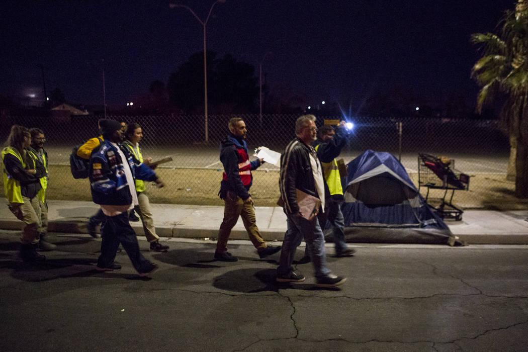 Voluntarios para el censo anual sin hogar del Condado de Clark caminan frente a un campamento en Veterans Memorial Drive en Las Vegas durante el censo anual de personas indigentes del Condado de C ...