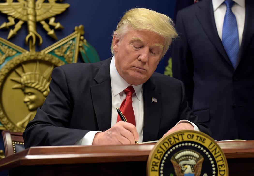 Presidente Donald Trump firma un documento en la Casa Blanca. Foto AP.