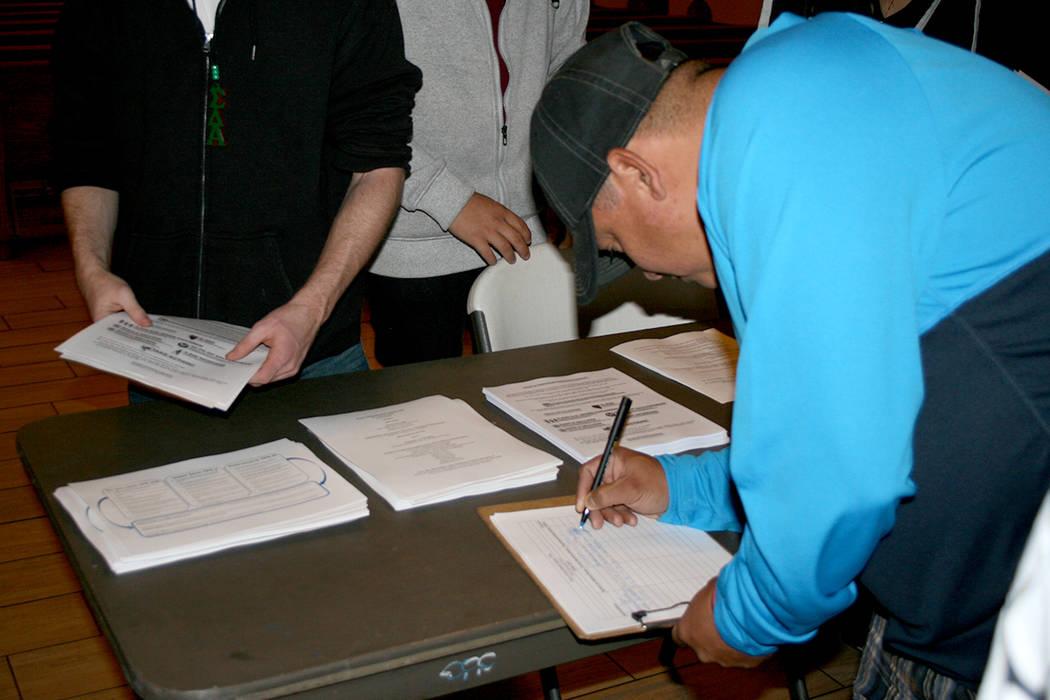 Un hombre llena un formulario para recibir ayuda en un evento de apoyo al programa TPS, el 28 de noviembre del 2017. | Foto Archivo/Valdemar González.