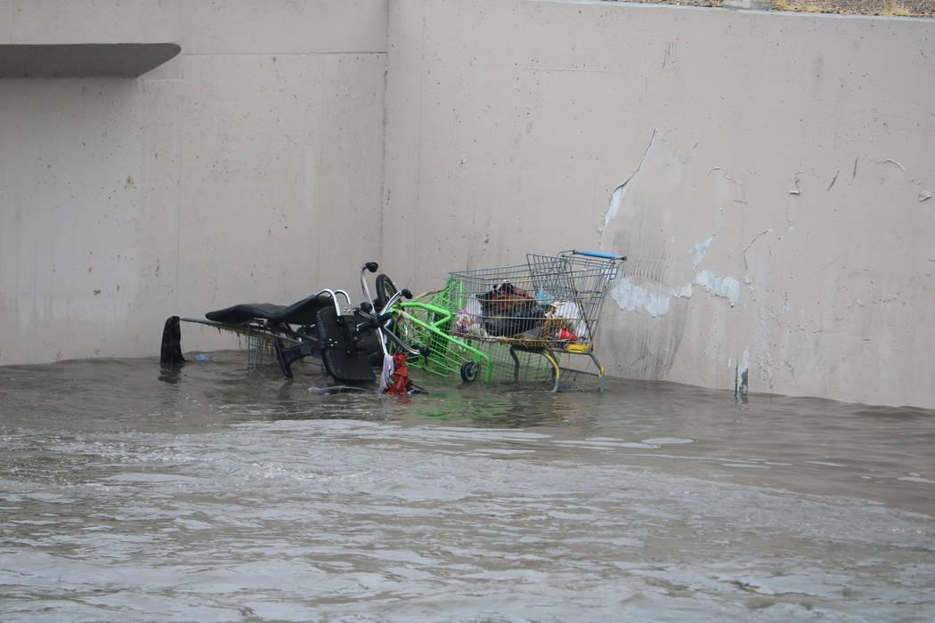 Los carritos de compras están medio sumergidos en las inundaciones a unos 100 metros por debajo del sitio donde las cuadrillas rescataron a un hombre y una mujer bajo un puente en East Carey Aven ...
