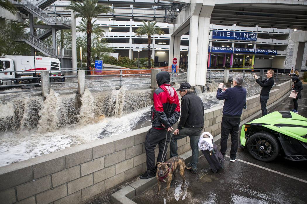 La gente mira las aguas de las inundaciones apresurarse en un canal pluvial cerca del Hotel The Linq en Las Vegas el martes 9 de enero de 2018. (Patrick Connolly / Las Vegas Review-Journal) @PConnPie