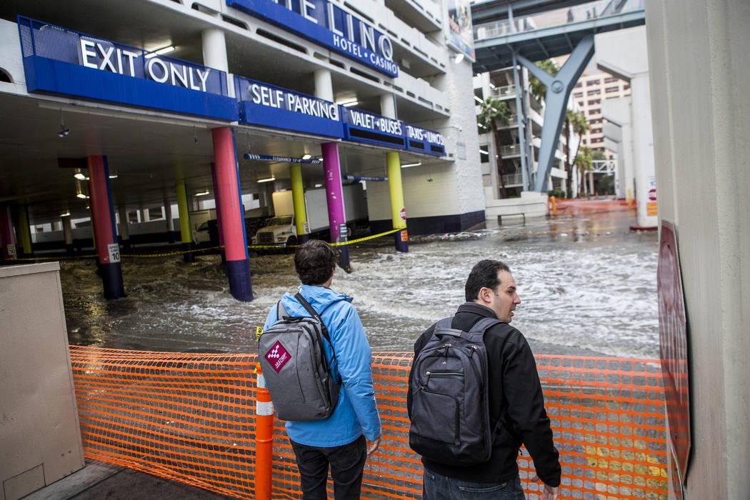 Jon, a la izquierda, y Ben Gaiser, que asisten al CES, miran cómo las inundaciones se precipitan en el The Linq Hotel de Las Vegas el martes 9 de enero de 2018. (Patrick Connolly / Las Vegas Revi ...