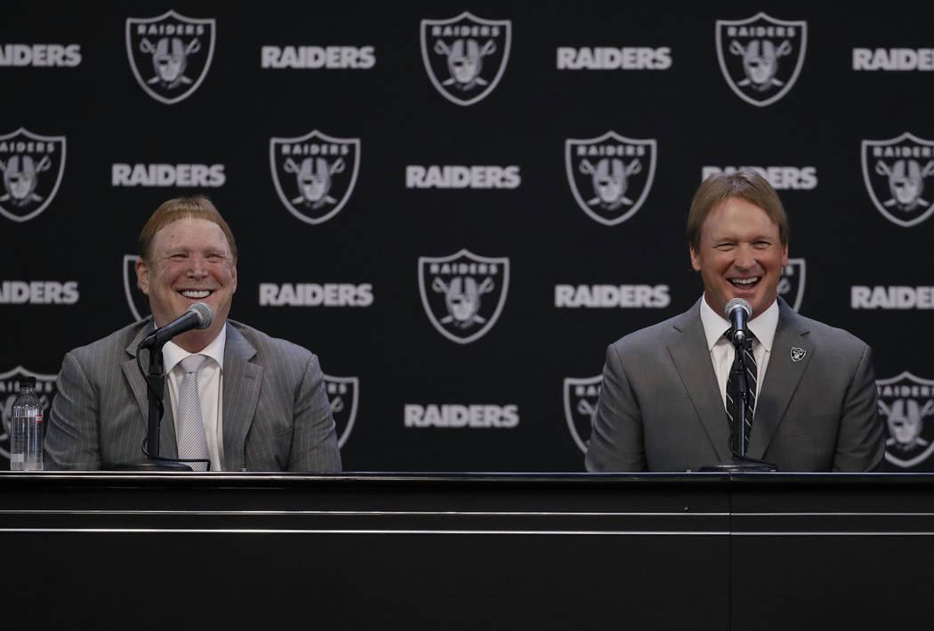 El nuevo entrenador en jefe de los Oakland Raiders, Jon Gruden, sonríe mientras escucha una pregunta del ex jugador de los Raiders Charles Woodson, sentado junto al propietario Mark Davis durante ...