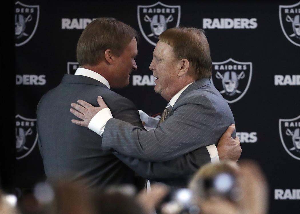 El propietario de los Oakland Raiders Mark Davis, a la derecha, abraza al nuevo entrenador en jefe Jon Gruden durante una conferencia de prensa de fútbol de la NFL el martes 9 de enero de 2018 en ...