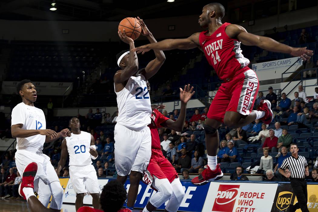 El guardia de la Fuerza Aérea Pervis Louder (22) busca una canasta mientras el guardia de la UNLV Jordan Johnson (24) se defiende durante un juego de baloncesto universitario de la NCAA en Air Fo ...
