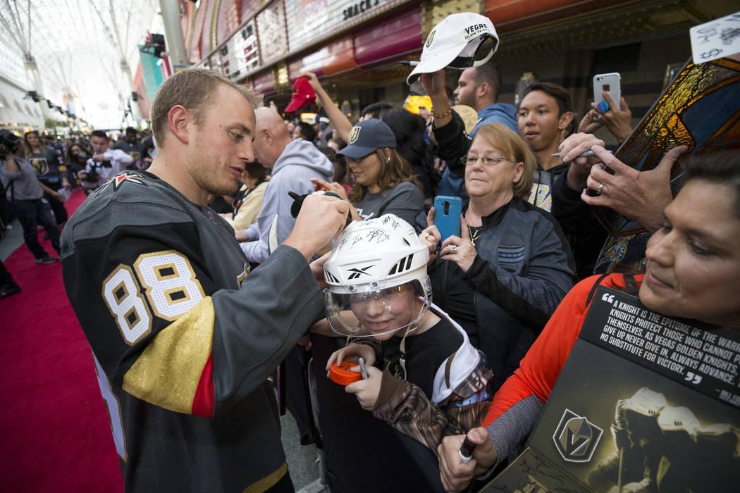 El defensa de Vegas Golden Knights Nate Schmidt (88) autografia el casco del residente de Las Vegas Hunter Klingenneier, 12, durante la primera fiesta de fanáticos del equipo en la Fremont Street ...