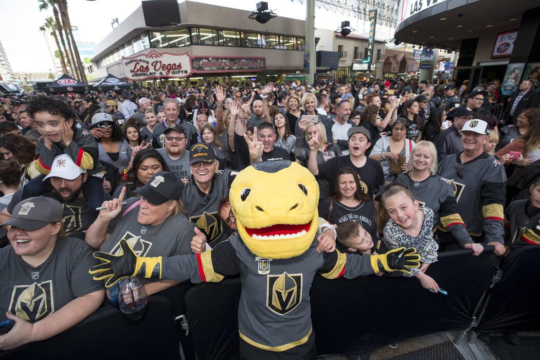 La mascota de Vegas Golden Knights, Chance the Golden Gila Monster, posa con los fanáticos durante la primera fiesta de los fanáticos del equipo en la Fremont Street Experience en el centro de L ...