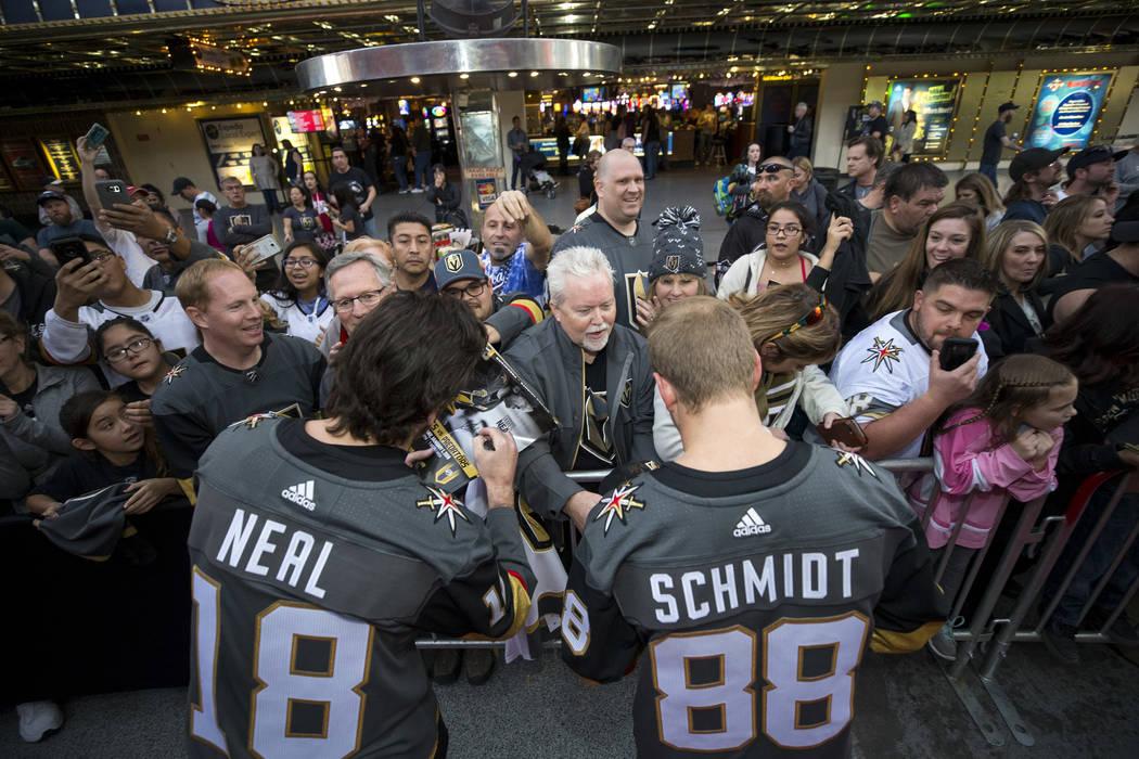 El ala izquierda de Vegas Golden Knights James Neal (18) y el defensa Nate Schmidt (88) firman autógrafos durante la primera fiesta de fanáticos del equipo en Fremont Street Experience en el cen ...