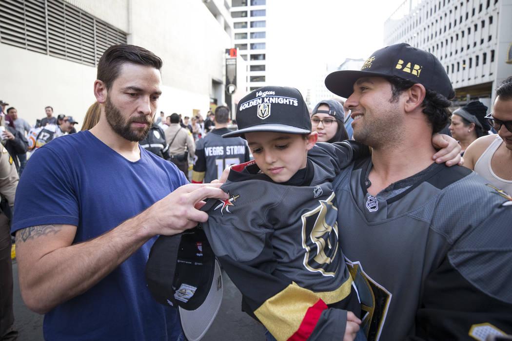 El defensa de Vegas Golden Knights Deryk Engelland, izquierda, firma la camiseta de Tristen Sterbens, de 6 años, mientras su padrastro, Mike Foskaris, lo abraza durante la primera fiesta de faná ...