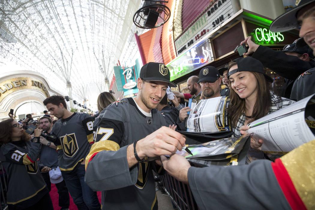 El defensaa de Vegas Golden Knights Shea Theodore (27) firma autógrafos durante la primera fiesta de admiradores del equipo en la Fremont Street Experience en el centro de Las Vegas el domingo 14 ...