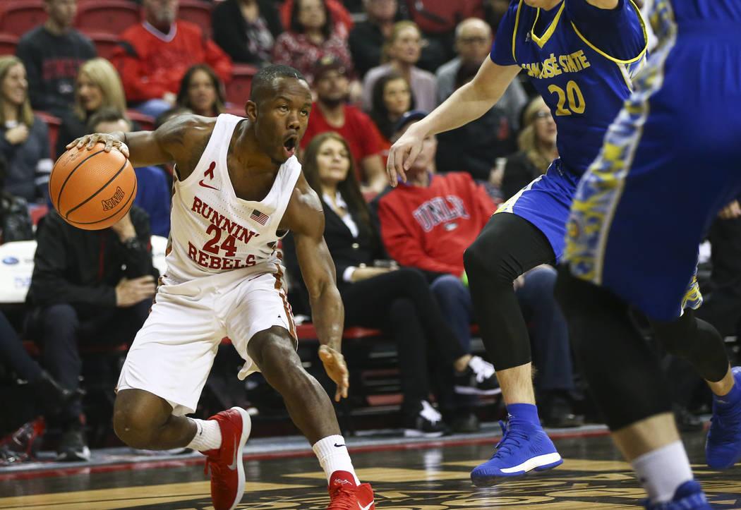 Bbase de UNLV Rebeldes Jordan Johnson (24) conduce el balón contra base Noah Baumann (20) de San José State Spartans  durante un partido de baloncesto en el Thomas & Mack Center en Las Vegas ...