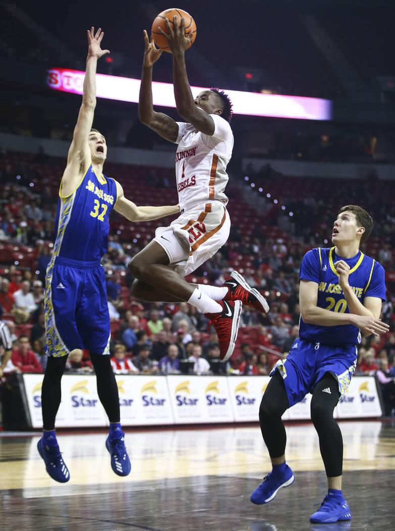 Base de UNLV Rebels Kris Clyburn (1) va a la canasta entre Ryan Welage, alero de los Spartans de San Jose State, y Noah Baumann, de 20 años, durante un partido de baloncesto en el Thomas & Ma ...