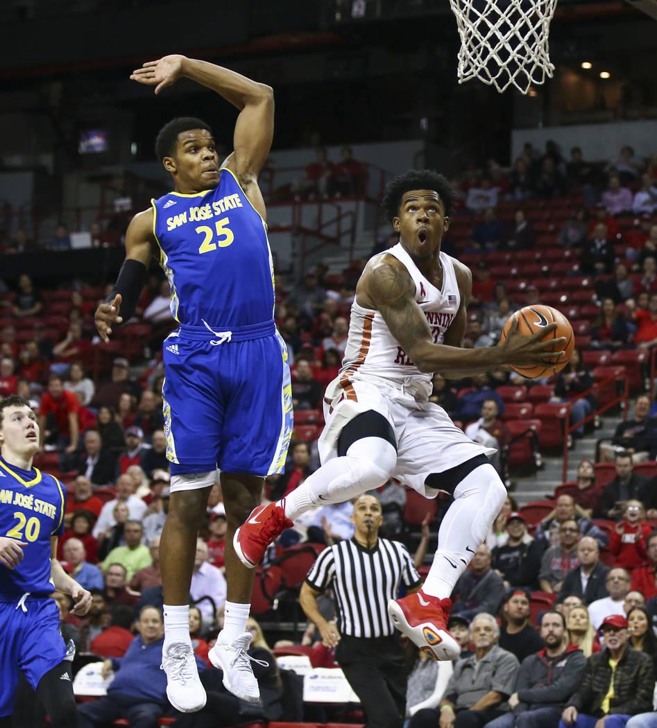 Base  de UNLV Rebels Jovan Mooring (30) sube para superar al base de los Spartans de San Jose Jaycee Hillsman (25) durante un partido de baloncesto en el Thomas & Mack Center en Las Vegas el m ...