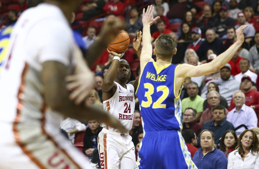 Base de UNLV Rebels Jordan Johnson (24) intenta dispararle al alero de los Spartans de San José State Ryan Welage (32) durante un partido de baloncesto en el Thomas & Mack Center en Las Vegas ...