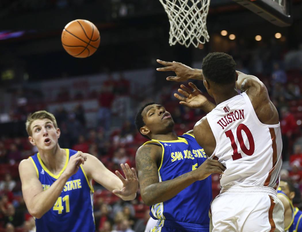 Shakur Juiston (10) de los Rebels de UNLV  envía un pase sobre el alero de los Spartans de San José State Keith Fisher III (5) y el centro Ashtin Chastain (41) durante un partido de baloncesto e ...