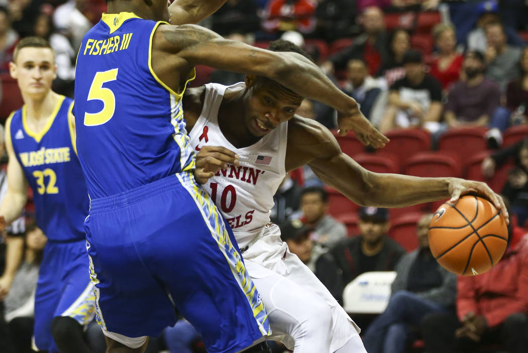 Alero de UNLV Rebels Shakur Juiston (10) va contra el alero de los Spartans de San José State  Keith Fisher III (5) durante un partido de baloncesto en el Thomas & Mack Center en Las Vegas el ...