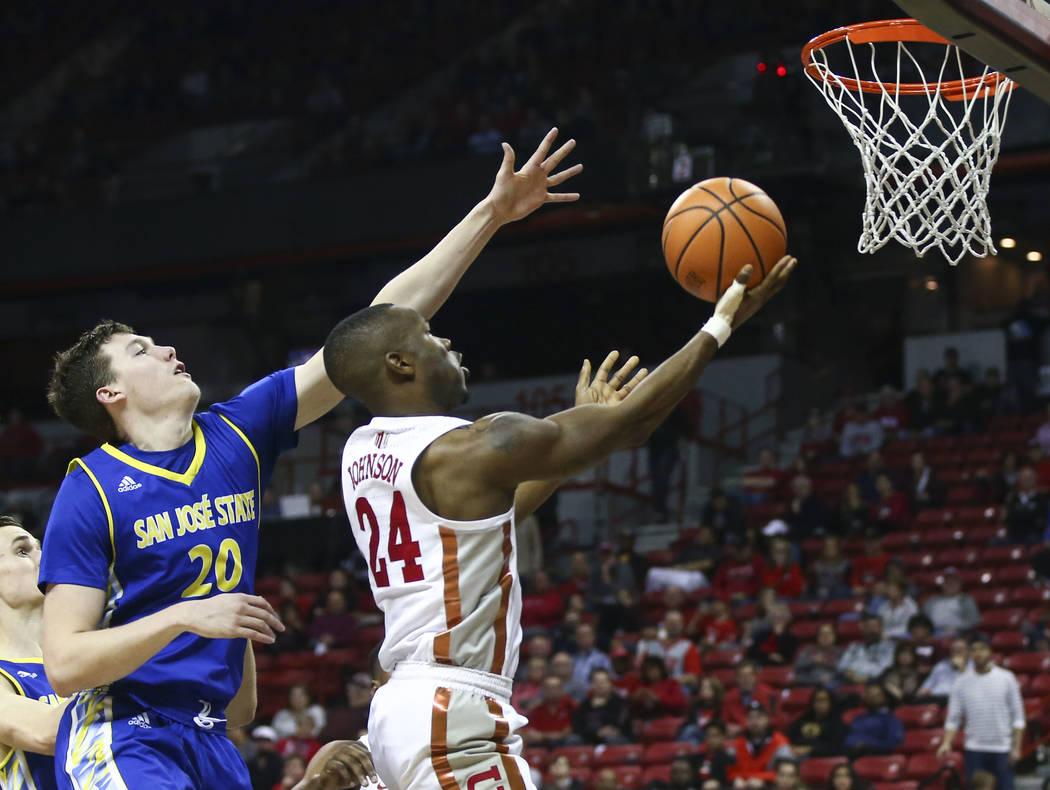 Base de UNLV Rebels Jordan Johnson (24) va a la canasta pasando a Noah Baumann (20), base de los Spartans de San José, durante un partido de baloncesto en el Thomas & Mack Center en Las Vegas ...